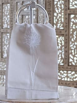 guest towel with dandelion motif in white on a tan linen blend